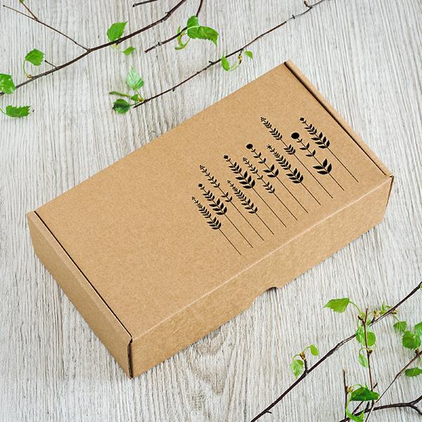 Kartona kaste ar lāzergrieztu pļavas attēlu