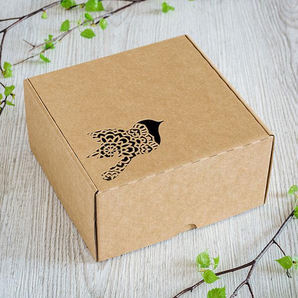 Kartona kaste ar lāzergrieztu putnu lidojumā