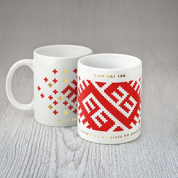 """Balta krūze ar sarkanu un zelta Latvijas ornamentu un tekstu: """"Mazakā ozola lapa un plaša kā pasaules sirds"""""""