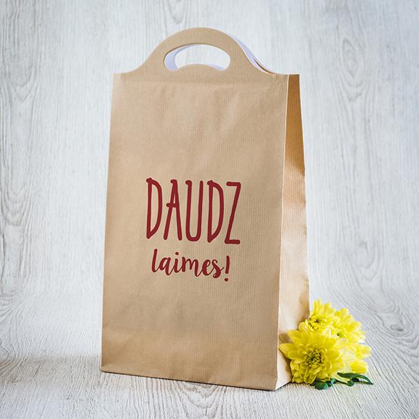 Gaišs dāvanu maisiņš ar sarkanu apdruku ar tekstu Daudz laimes