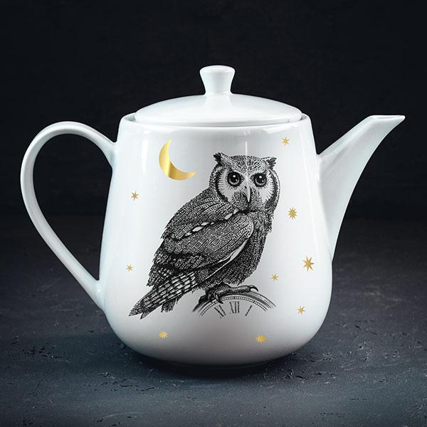 Balta tējas kannaar melnu pūces zīmējumu un zelta elementu