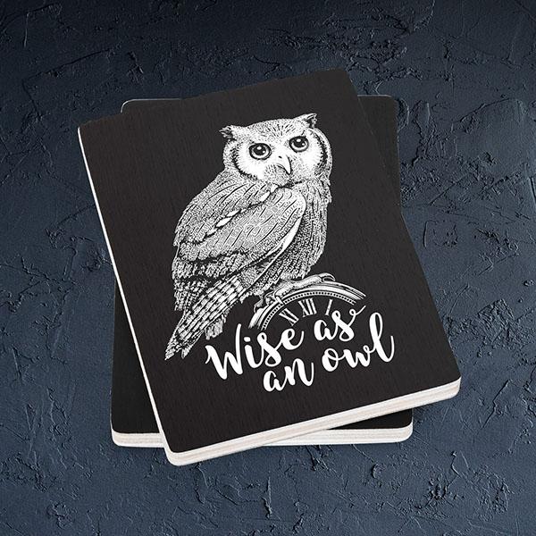 """Melns magnēts ar baltu pūces zīmējumu un tekstu: """"Wise as an owl"""""""
