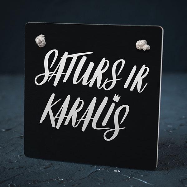 """Melns dekoratīvais dēlītis ar baltu tekstu: """"Saturs ir karalis"""""""
