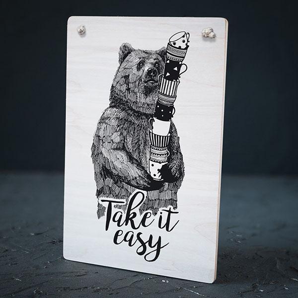 """Balts dekoratīvais koka dēlītis ar melnu lāča zīmējumu un tekstu: """"Take it easy!"""""""