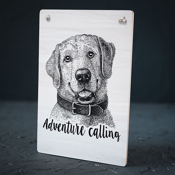 """Balts dekoratīvais koka dēlītis ar melnu suņa zīmējumu un tekstu: """"Adventure calling"""""""