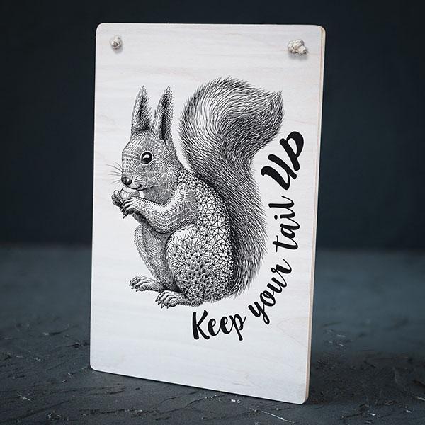 """Balts dekoratīvais koka dēlītis ar melnu vāveres zīmējumu un tekstu: """"Keep your tail up"""""""