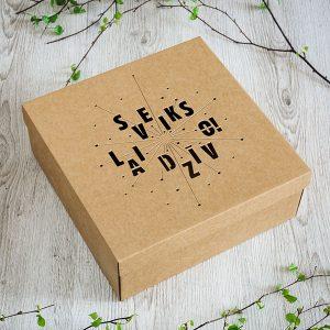 """Kartona kaste ar lāzergravētu tekstu: """"Sveiks lai dzīvo!"""""""