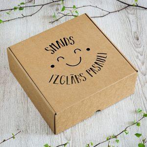"""Kartona kaste ar lāzergravētu tekstu: """"Smaids izglābs pasauli"""""""