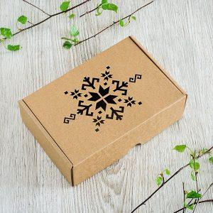 Kartona kaste ar lāzergravētu latvju zīmes zīmējumu.