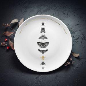 """Vidējais šķīvis ar melnu kukaiņu zīmējumu un zelta elementu un tekstu: """"Kukaiņi ragaiņi"""""""
