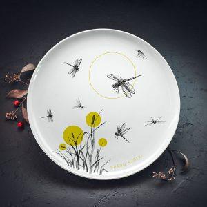 """Lielais šķīvis ar melnām spārēm un zaļiu augu zīmējumu un tekstu: """"Spāru svētki"""""""
