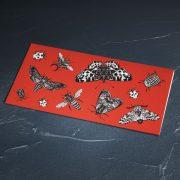 naudas aploksne sarkanā krāsā ar kukaiņiem