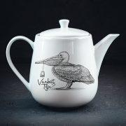 Porcelāna tējkanna baltā krāsā, tilpums 1200ml, ar attēlotu pelikānu, kurš knābī tur tējas maisiņu un jautājumu- varbūt tēju