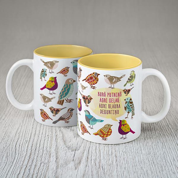"""Balta kafijas krūze ar putnu zīmējumu un krāsainu tekstu: """"Kurs putniņš agri ceļas, agri slauka deguntiņu!"""""""