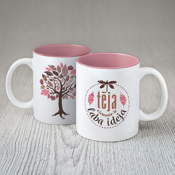 """Balta krūze ar rozā koka zīmējumu un krāsainu tekstu: """"Tēja vienmēr ir laba ideja"""""""