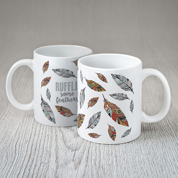 """Balta krūze ar krāsainām spalvām tekstu angļu valodā: """"Ruffle some feathers"""""""