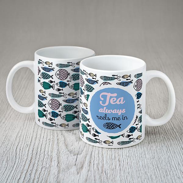 """Balta krūze ar krāsainu zivju zimējumu un tekstu angļu valodā: """"Tea always reels me in"""""""