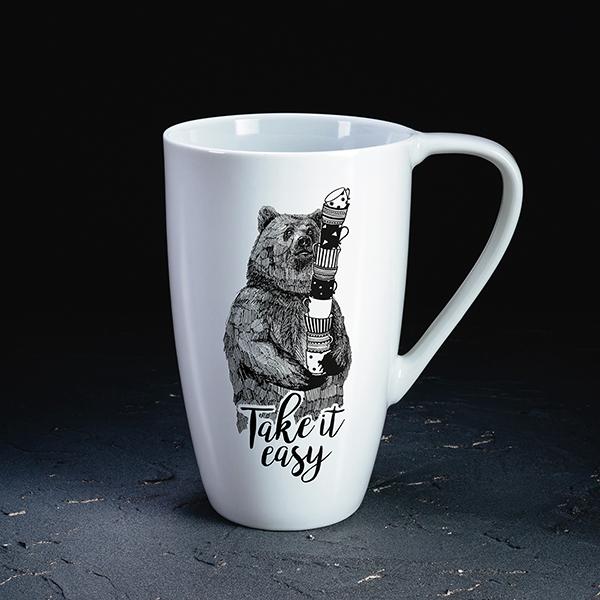 """Balta krūze ar melnu lāča zīmējumu un tekstu angļu valodā: """"Take it easy!"""""""