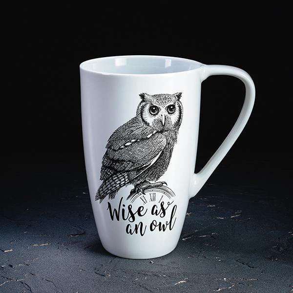 """Balta krūze ar melnu pūces zīmējumu un tekstu angļu valodā: """"Wise as an owl!"""""""