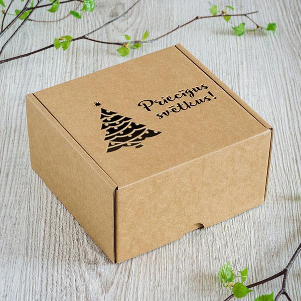 """Kartona kaste ar lāzergrieztu egles zīmējumu un tekstu: """"Priecīgus svētkus!"""""""