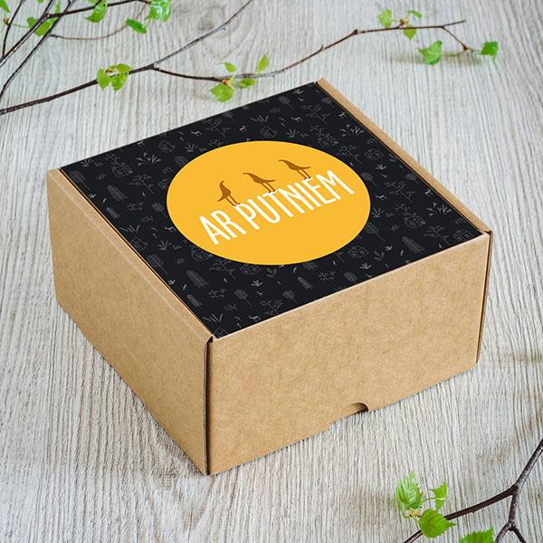 """Gaiša kartona kaste ar krāsainu uzlīmi un tekstu: """"Ar putniem"""""""