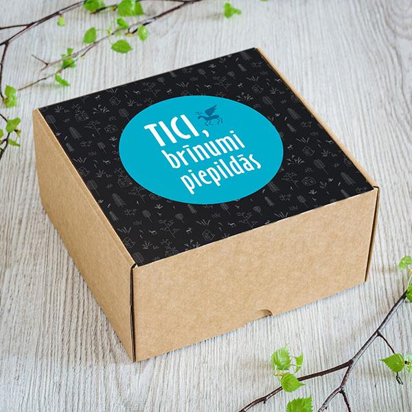Maza dāvanu kaste ar melnu un zilu fonu un baltu apdruku ar tekstu Tici, brīnumi piepildās