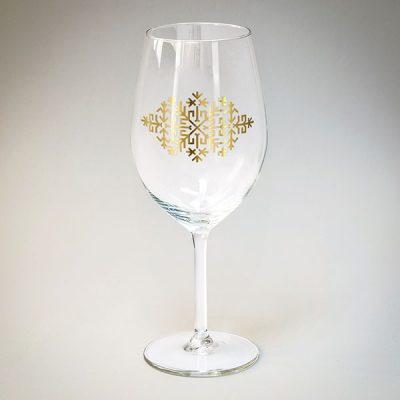 Vīna glāze ar zelta Austras koka zīmējumu.