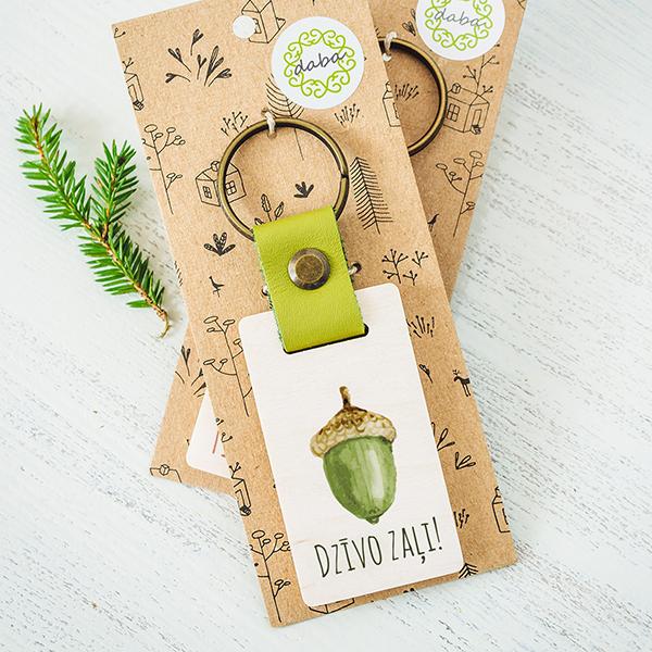 Atslēgu piekariņš ar zaļu zīli ar tekstu Dzīvo zaļi