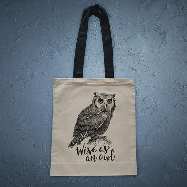 Bēša soma ar melnu apdruku ar pūci ar tekstu Wise as an owl