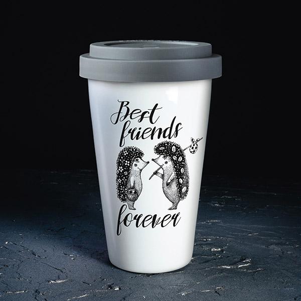 """Balta ceļojumu krūze ar melnu divu ežu zīmējumu, kā arī pelēku plastasas vāciņu un tekstu angļu valodā: """"Best friends forever!"""""""