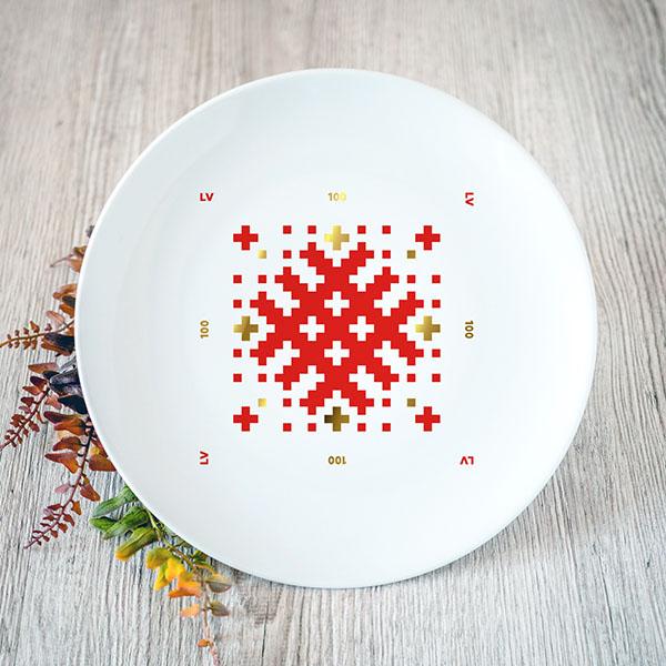 Balts šķīvis ar sarkanu un zelta Latvijas ornamentu
