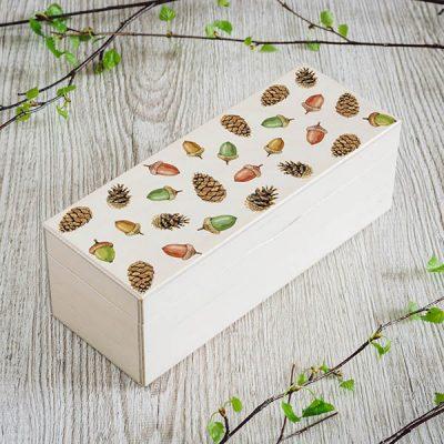 Balta koka kaste ar čiekuru un zīļu apdruku, kā arī kastei ir 1 rinda un rindā 3 nodalījumi