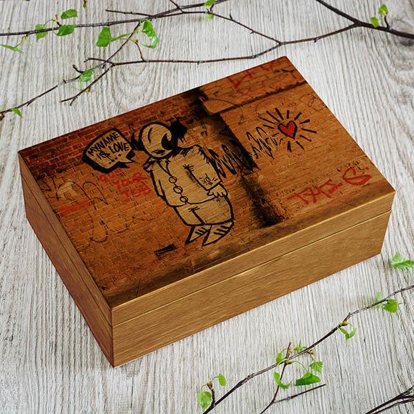 "Gaiši brūna koka kaste ar gaffiti zīmējumu un tekstu: ""My name is love"""