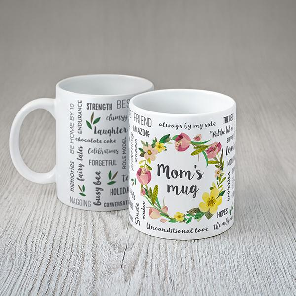 """Balta krūze ar krāsainiem tekstiem angļu valodā: """"Mom's mug"""""""