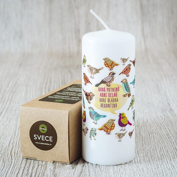 Balta svece ar krāsainu apdruku ar putniem ar tekstu Kurš putniņš agri ceļas, agri slauka deguntiņu