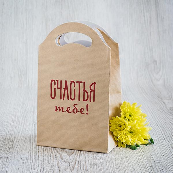 Gaišs dāvanu maisiņš ar sarkanu apdruku ar tekstu krievu valodā Daudz laimes