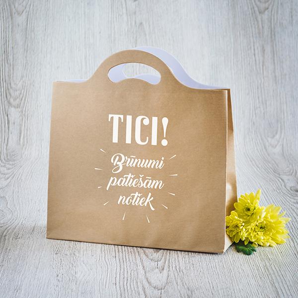 Gaišs dāvanu maisiņš ar baltu apdruku ar tekstu Tici, brīnumi patiešām notiek