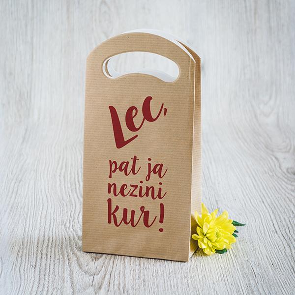 Gaišs dāvanu maisiņš ar sarkanu apdruku ar tekstu Lec, pat ja nezini kur