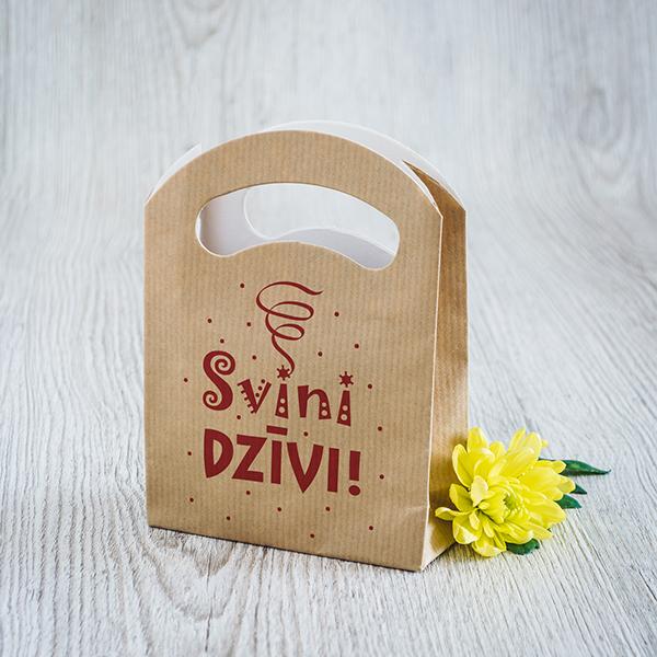 Gaišs dāvanu maisiņš ar sarkanu apdruku ar tekstu Svini dzīvi