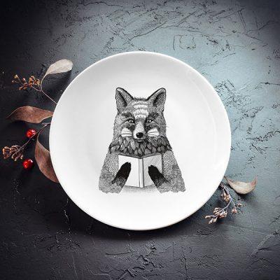 Balts mazais šķīvis ar melnu lapsas zīmējumu.