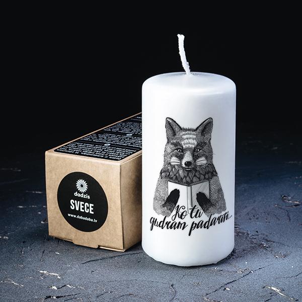 Balta svece ar melnu apdruku ar lapsas zīmējumu ar tekstu Ko tu gudram padarīsi?