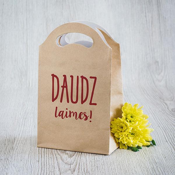 Gaišs dāvanu maisiņš ar sarkanu tekstu Daudz laimes