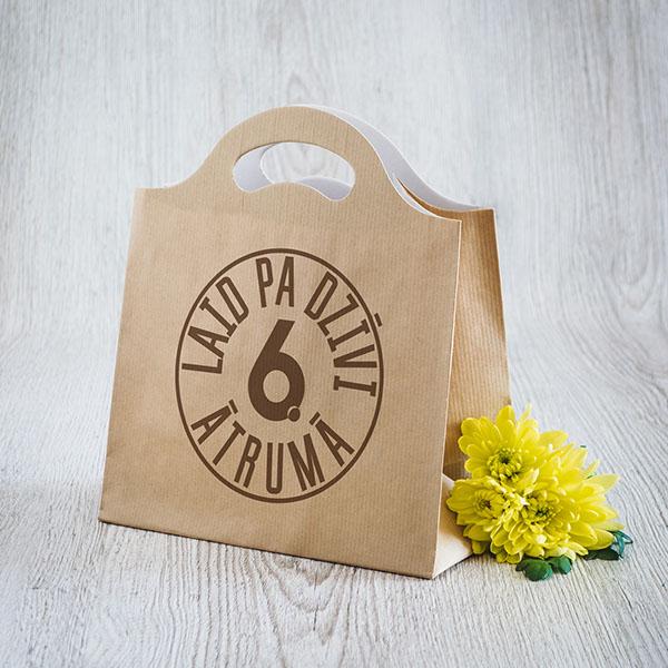 Gaišs dāvanu maisiņš ar brūnu tekstu Laid pa dzīvi 6 ātrumā