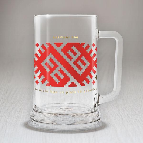 """Alus kauss ar sarkanu un zelta Latvijas ornamentu un tekstu: """"Maza kā ozola lapa, plaša kā pasaules sirds"""""""