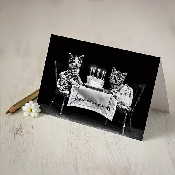 Atverama kartīte ar melnu fonu un diviem kaķīšiem pie galda