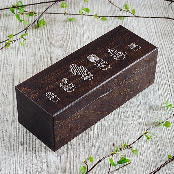Tumši brūna koka kaste ar baltu kaktusu zīmējumu, kastei ir 1 rinda un rindā 3 nodalījumi