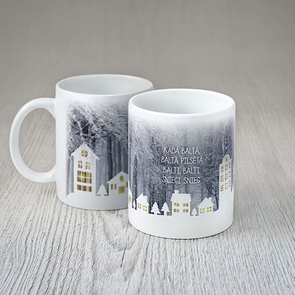 """Balta krūze ar krāsainu pilsētu sniegā apdruku un tekstu: """"Kādā baltā, baltā pilsētā balti, balti sniegi snieg"""""""