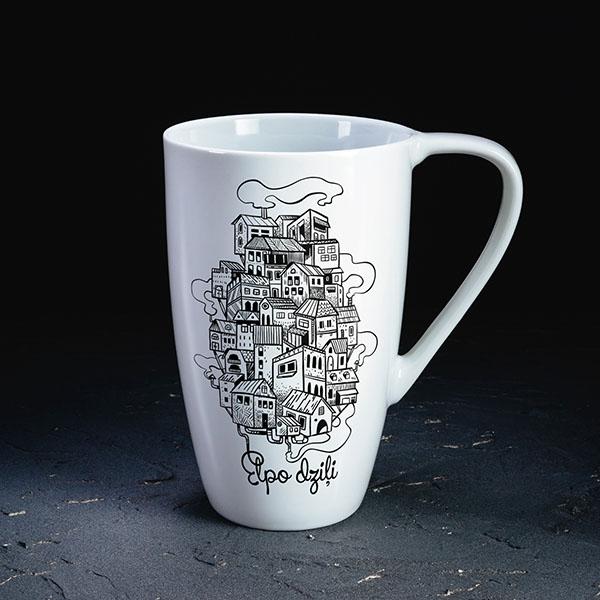 """Balta krūze ar pilsētas zīmējumu un tekstu: """"Elpo dziļi"""""""