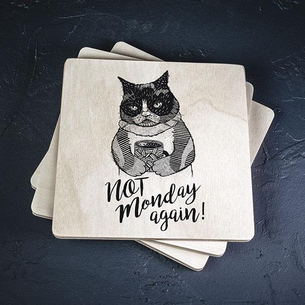 """Balts krūžu paliktnis ar melnu kaķa zīmējumu un tekstu: """"Not Monday again!"""""""