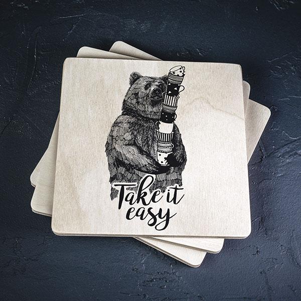 """Balts krūžu paliktnis ar melnu lāča zīmējumu un tekstu: """"Take it easy"""""""